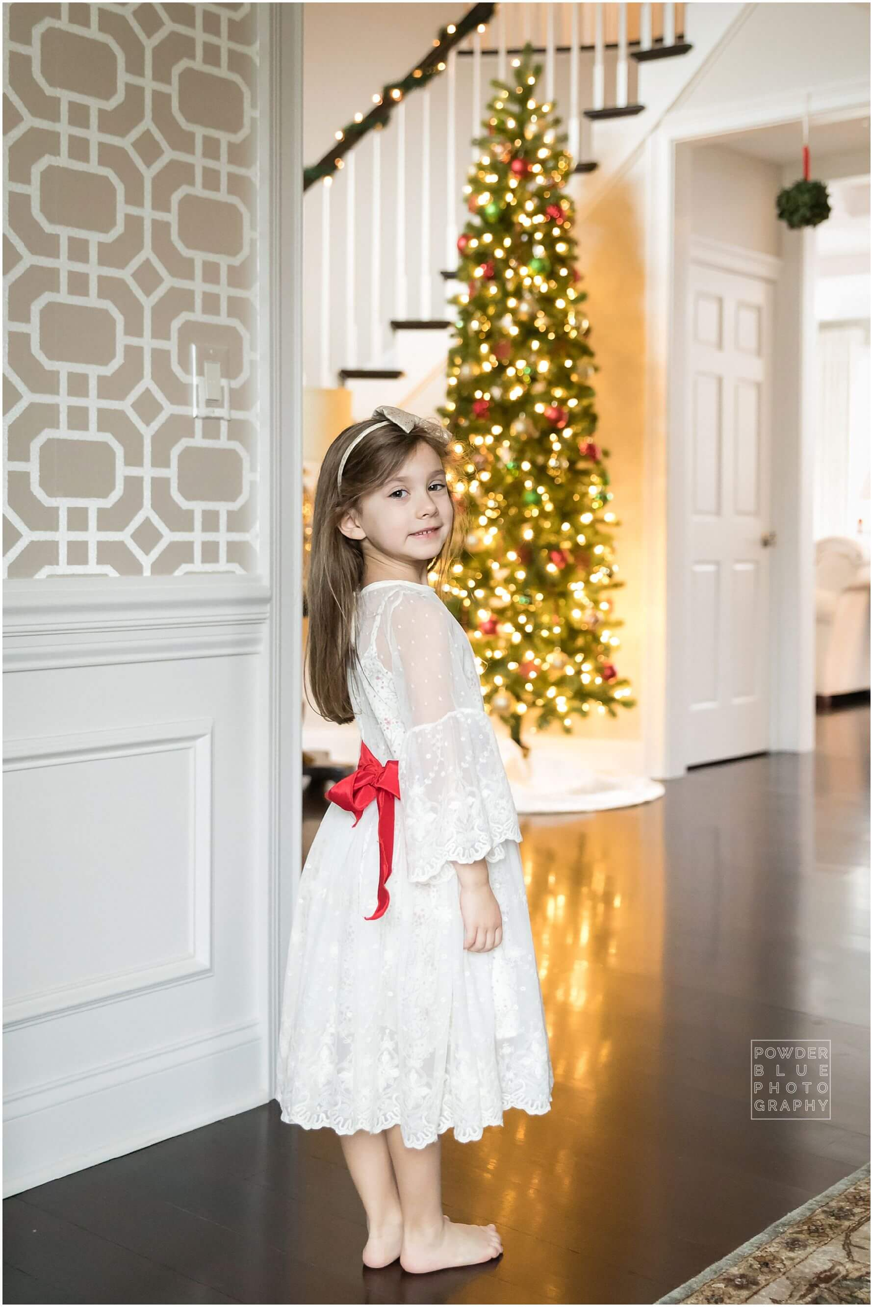 little girl in front of christmas tree with chasing fireflies dress.