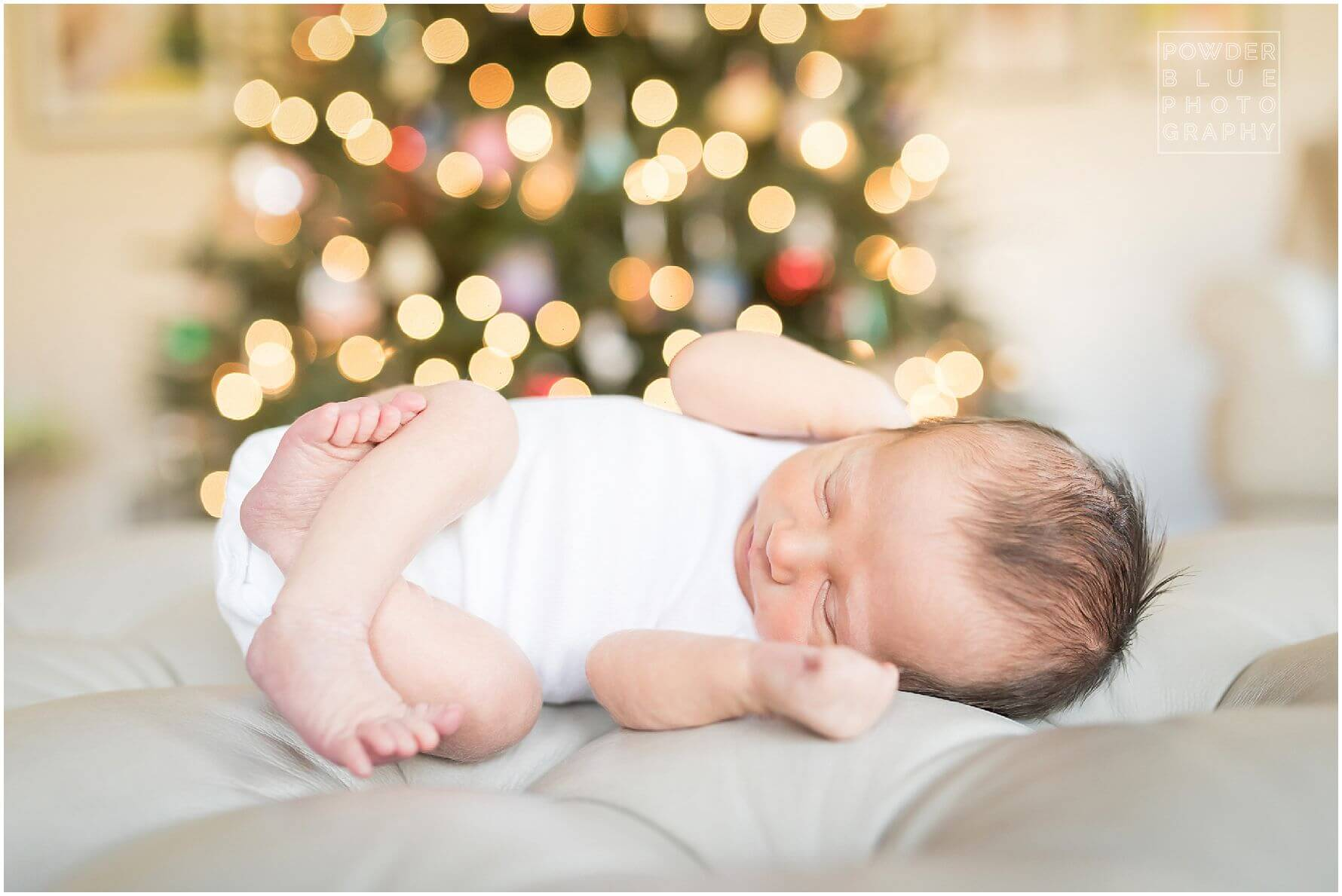 pittsburgh newborn photographer missy timko photographed this baby iboy in front of the christmas tree with twinkling lights behind him. wide open aperture with christmas tree as backdrop.